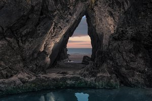 Beach sunset through a cave opening