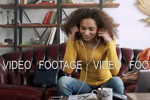 young latin curly woman speak with friend by telephone mobile using handsfree earpieces