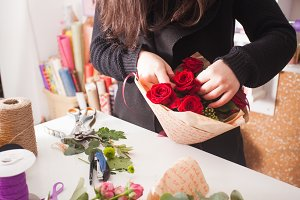 Florist making  bouquet of red roses