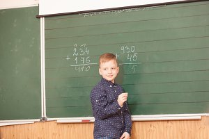 School boy solves examples at the board