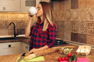Woman drinks coffee in the morning before preparing breakfast
