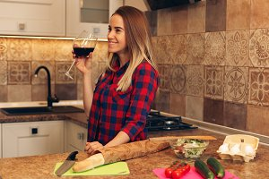 Pretty woman drinking some wine at home in kitchen.