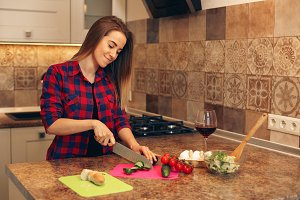 Portrait of smiling young housewife in modern kitchen