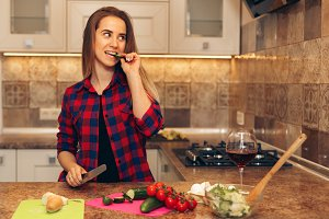 Happy young woman eating slice of cucumber in the kitchen