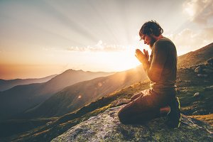 Man praying at sunset mountains