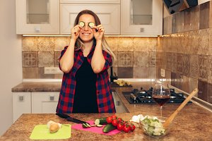 Happy woman having fun with cucumber at kitchen