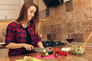 Woman making salad in kitchen