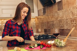 Young woman preparing healthy salad and smiling