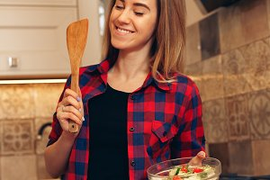Cheerful young woman is cooking in the kitchen with joy