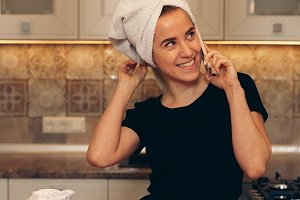Woman with a towel on her head talking on the phone and preparing breakfast