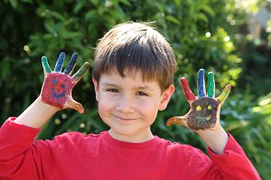 little kid showing his painted hands