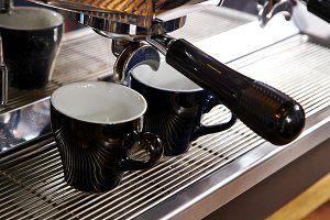 Espresso pouring in cups from coffee machine