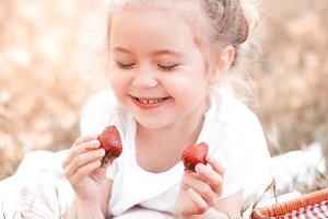 Smiling girl eating strawbrry