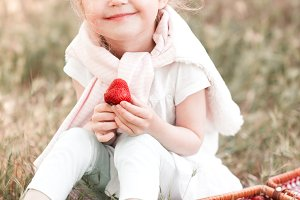 Cute girl eating berry