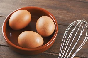 Eggs and cookware on wooden table. Horizontal shoot.