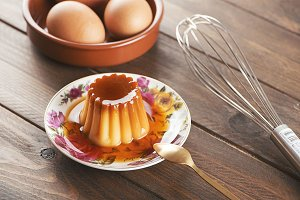 Flan on a colorful plate next to eggs and cookware on wooden table.