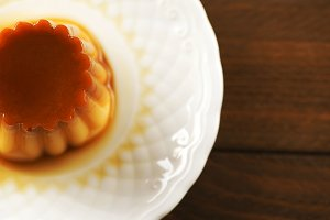 From above white plate with flan on the wooden background. Horizontal shoot ..