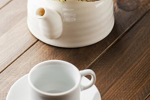 From above white ceramic mug and pot placed on the wooden background.