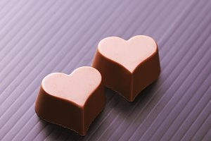 Close-up of chocolates with heart shape on black background.