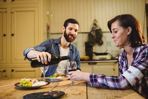 Man pouring wine in glass to woman