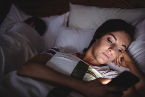 Woman using mobile phone while lying on bed