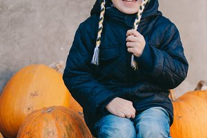 little boy on pumpkins
