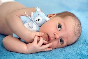 newborn lies with the blue soft toy bear on the bed