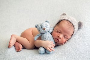 newborn boy in a naked hat lies on a light blanket