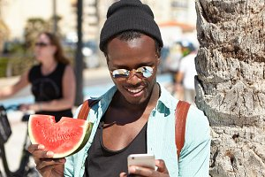 Happy African American tourist eating fresh juicy watermelon and using 3g or 4g internet connection on mobile phone while relaxing on beach, standing at palm tree, reading messages from friends