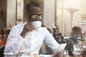 Always connected. Business, modern technology and communication. Candid shot of successful stylish black entrepreneur in round sunglasses having morning cappuccino at coffee shop, using cell phone