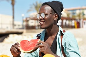 Joyful happy fashionable young Afro American man having picnic on beach with friends, holding slice of ripe watermelon, looking towards sea with broad smile, watching dolphins playing in water