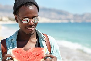 Close up outdoor portrait of handsome carefree smiling African American male traveler in trendy shades and hat walking by the sea and eating fresh ripe watermelon against blue water background