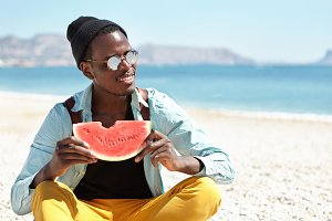 People and lifestyle. Travel and tourism. Outdoor shot of happy relaxed young Afro American man backpacker enjoying sweet juicy watermelon, sitting cross-legged on pebble beach, holding ripe fruit