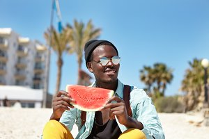Cheerful young African American male dressed in trendy clothes having nice time outdoors by the sea, enjoying ripe juicy watermelon and good sunny weather, smiling broadly, admiring beautiful seascape