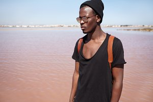 People, lifestyle, travel and fashion concept. Attractive fashionable young African American male model wearing black low-neck t-shirt, hat and mirrored lens shades posing outdoors by the sea