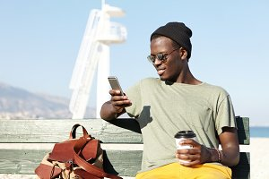 Outdoor portrait of fashionable smiling African American male tourist enjoying coffee out of paper cup and searching for new interesting places on websites using online application on mobile phone