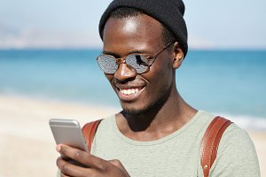 Modern technology, lifestyle, travel and tourism. Happy Afro American male traveler typing text message on smart phone, looking at screen with broad smile during walk at seaside on sunny summer day