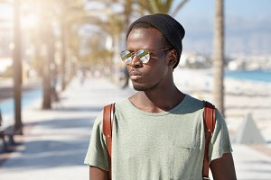 Confident serious African American 20-year old man with backpack walking along street on summer sunny day. Black hipster in hat and mirroerd lens sunglasses going to beach at daytime in resort town