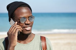 Handsome happy Afro American student wearing round shades and hat smiling broadly, talking on mobile phone to his parents, saying that he is doing ok while traveling alone during summer holidays