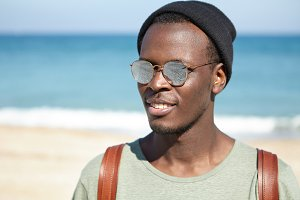 Portrait of cheerful black man traveler enjoying summer vacations by the sea, looking carefree and relaxed, wearing trendy hat and mirrored lens sunglasses. Tourism, travel, people and lifestyle