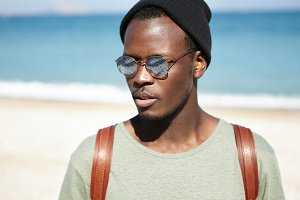People, lifestyle, travel and adventure concept. Close up shot of attractive young African American tourist with backpack, having nice walk along seashore, blue water and white sand in backgrond