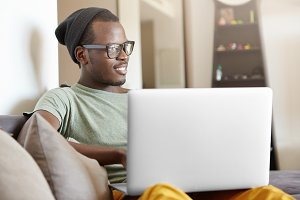 Carefree and relaxed young dark-skinned student in hat and glasses relaxing at home after college, sitting on couch with laptop pc on his lap, playing video games or watching favourite series online