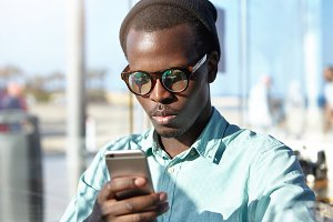 Indoor portrait of serious concentrated Afro American young man reading urgent text message on mobile phone. Dark-skinned male in trendy glasses and hat using modern portable electronic gadget indoors