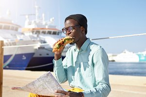 Attractive young black male tourist in stylish hat and eyewear enjoying fastfood by the sea on sunny day in resort town after long exhaustible walk, holding paper map and deciding where to go next