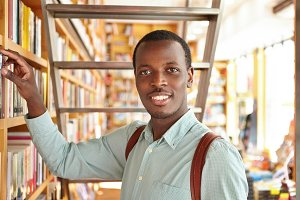 People, leisure and education. Curious Afro American student searching for book in library while doing research. Black tourist choosing phrasebook from shelf in bookshop during vacations abroad