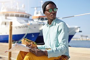 Fashionable young African American male tourist wearing stylish clothing and accessories traveling abroad, sitting against yachts background, holding sandwich in one hand and paper map in other
