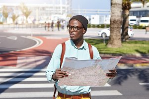 Handsome young Afro American tourist in eyewear and headdress having worried facial expression, looking for right direction using paper map while got lost in urban surroundings in foreign city