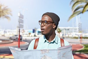 Stylish young African male traveler looking shocked and impressed with amazing modern architecture while exploring tourist destination during summer vacations abroad. People and tourism concept