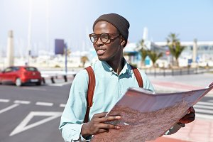 People, lifestyle, travel, adventure and tourism. Attractive happy black traveler with backpack studying city guide, exploring locations and streets in resort town, wearing stylish hat and glasses