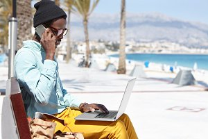 Trendy-looking Afro American designer sitting on bench outdoors by the sea working remotely on laptop computer and having phone conversation on sunny day while spending holidays in resort town